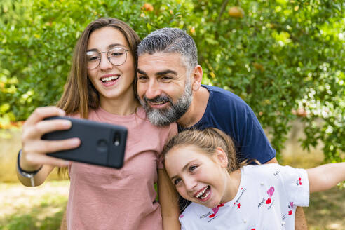 Happy father with two daughters taking selfie in garden - MGIF00728