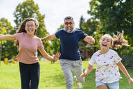 Carefree father with two daughters running on a meadow - MGIF00731