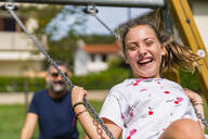 Portrait of happy girl on a swing with father in background - MGIF00734