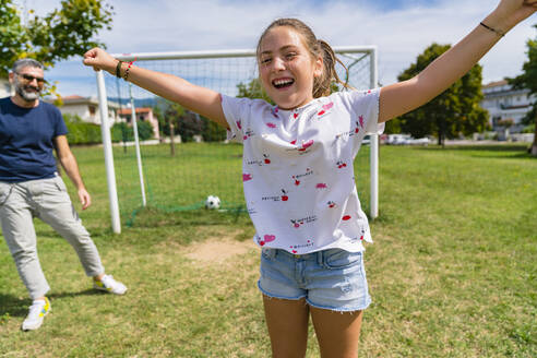 Happy girl playing football with father on a meadow - MGIF00737