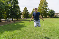 Happy man skipping rope in a park - MGIF00740