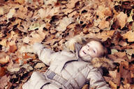 Girl lying in a heap of leaves in autumn forest - XCF00258