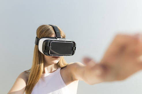Young woman using Vr googles, reaching with her hand - JPTF00329
