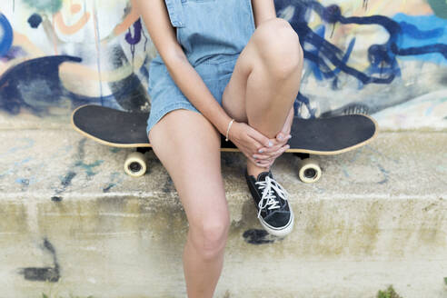 Young woman sitting on skateboard in front of graffiti - JPTF00332