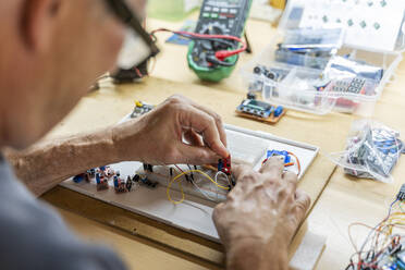 Senior man working on electronic circuits in his workshop - AFVF04015