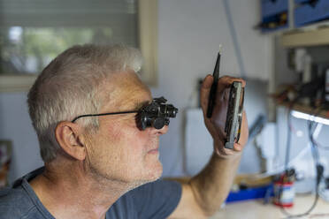 Senior man working on electronic circuits in his workshop - AFVF04018