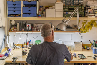 Senior man working on electronic circuits in his workshop - AFVF04021