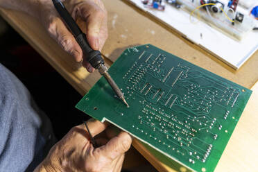 Senior man working on electronic circuits in his workshop, close up - AFVF04024
