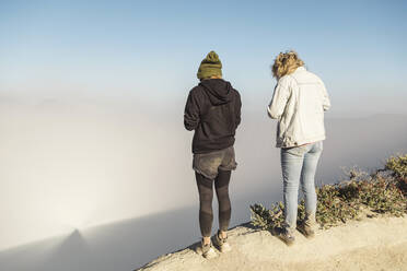 Young women with respirator masks standing at the edge of volcano Ijen, Java, Indonesia - KNTF03602