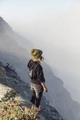 Young woman with respirator mask standing at the edge of volcano Ijen, Java, Indonesia - KNTF03605