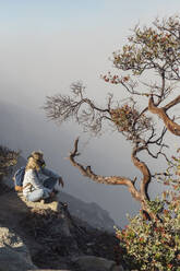 Woman with respirator mask sitting at volcano Ijen, Java, Indonesia - KNTF03608