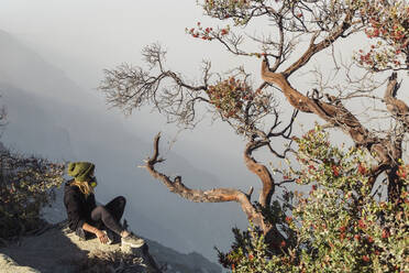 Woman with respirator mask sitting at volcano Ijen, Java, Indonesia - KNTF03611