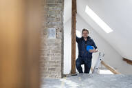 Architct standing on construction site of a loft conversion - GUSF02655