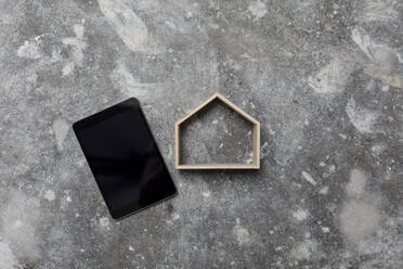 Digital tablet and wooden house model on gray ground - GUSF02673
