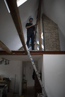 Architect working on construction sit of a loft conversion - GUSF02679