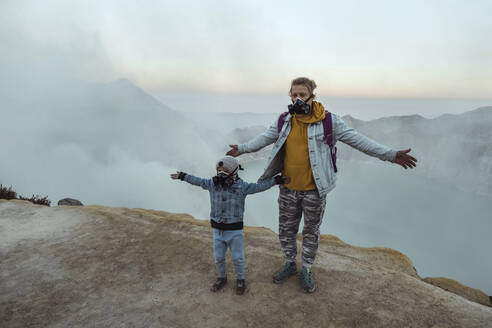 Father and son with respirator masks standing at the edge of volcano Ijen, Java, Indonesia - KNTF03614