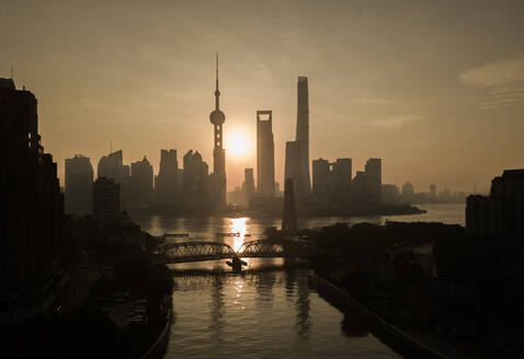 Aerial view of Shanghai skyline at sunset with passing Huangpu river, China. - AAEF04462
