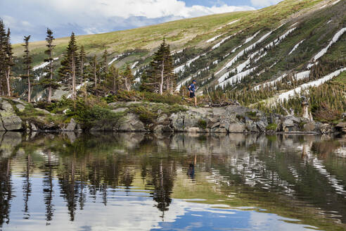 Man trail runs on lake shore in Indian Peaks Wilderness, Colorado - CAVF63400