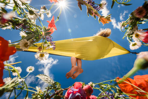 Girl relaxing in a hammock surrounded by flowers on a sunny day - CAVF63469
