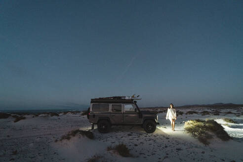 Girl walking close to the 4x4 during the blue hour - CAVF63769