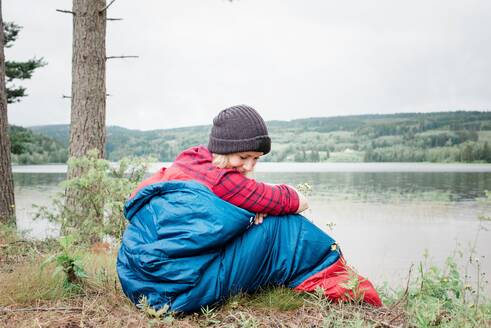 Woman sitting in a sleeping back enjoying the view camping on holiday - CAVF63919
