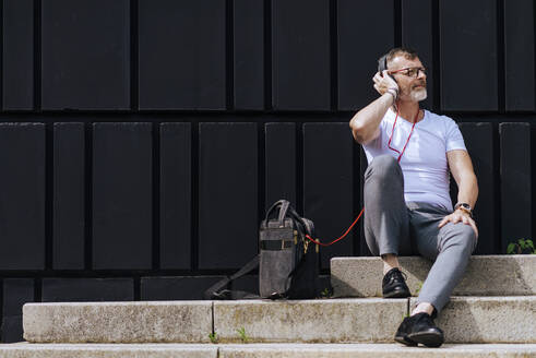 Bearded mature man sitting on steps with headphones while relaxing on a sunny day - CAVF64294
