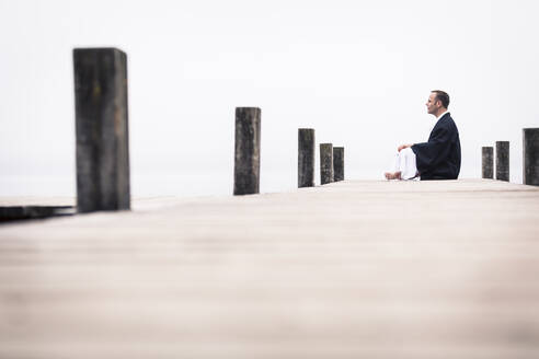 Man sitting on jetty doing yoga exercise, Lake Starnberg, Germany - WFF00091