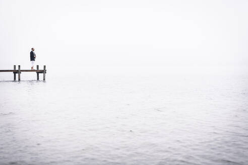 Barefoot man meditating on jetty at Lake Starnberg, Germany - WFF00094