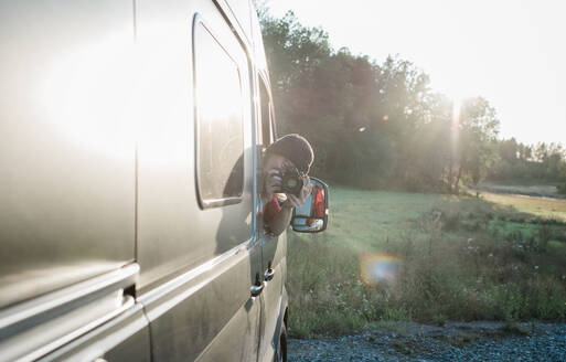 Woman leaning out of a camper van taking a picture with a dslr - CAVF64347