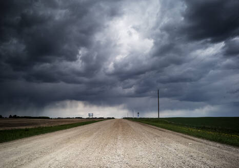 Storm clouds roll over a gravel road. - CAVF64392