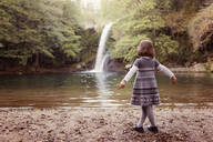 Young girl standing at a waterfall - XCF00263