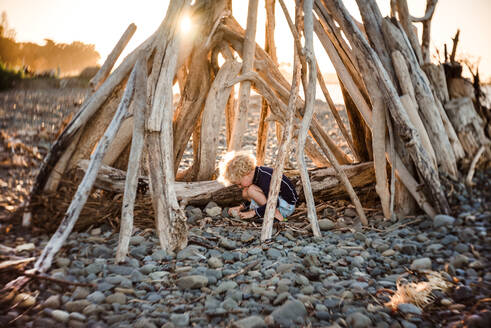 Small child playing in driftwood structure at dusk - CAVF64501