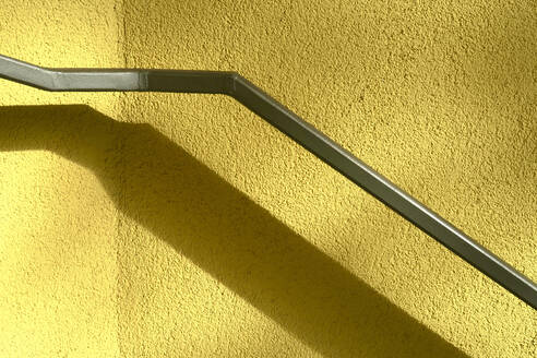 Shadow of handrail on yellow wall - JTF01359