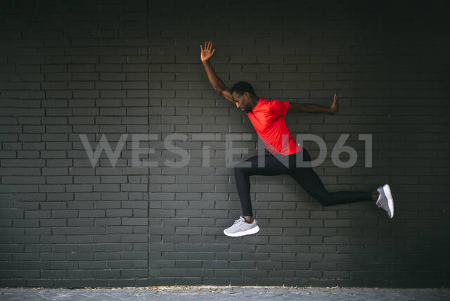 Young sportive man jumping in front of a brick wall - OCMF00759 - Oscar Carrascosa Martinez/Westend61