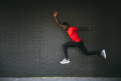 Young sportive man jumping in front of a brick wall - OCMF00759