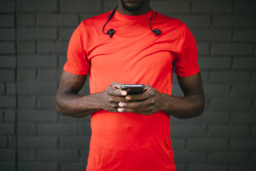 Young sportive man standing in front of a brick wall using his smartphone - OCMF00768