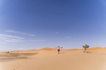 Overweight man with swimming shorts running in the desert of Morocco - OCMF00784