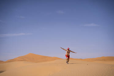 Overweight man with swimming shorts running in the desert of Morocco - OCMF00787