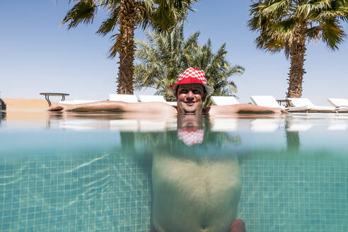 Overweight man with hat bathing in pool - OCMF00790