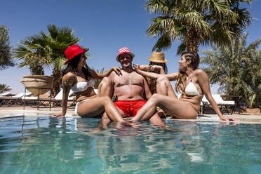 Overweight man surrounded by affectionate beautiful women at the poolside - OCMF00796