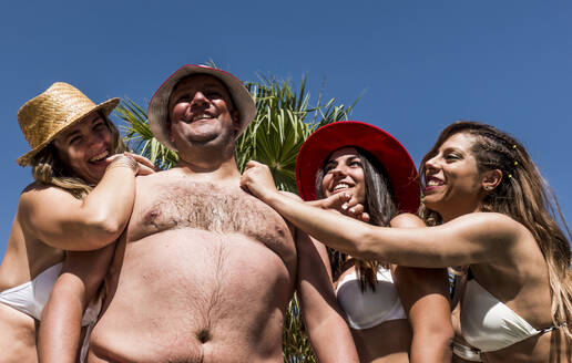 Overweight man surrounded by happy beautiful women - OCMF00799