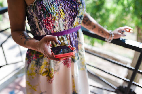 Wedding guest using smatphone dressed in colorful dress - CAVF64648