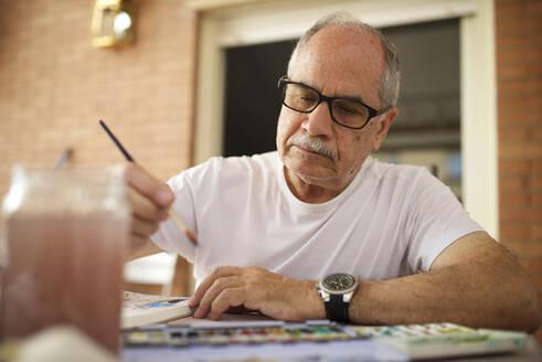 Senior man painting watercolor. - CAVF64675