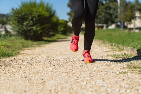 Close-up of woman running on stony path - MGIF00748