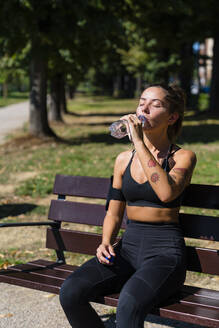 Sporty young woman having a cooling break on park bench - MGIF00757