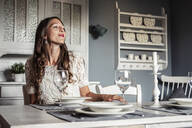 Smirking young woman sitting at laid table in country style kitchen - WFF00104