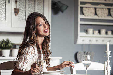 Portrait of smiling young woman sitting at laid table in country style kitchen - WFF00107