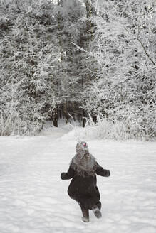 Back view of little girl running on snow field - EYAF00493