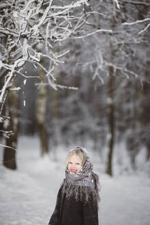 Portrait of happy little girl wearing headscarf standing in front of winter forest - EYAF00496