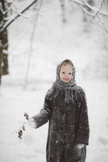 Portrait of little girl wearing headscarf and coat standing in winter forest holding twig with autumn leaves - EYAF00502